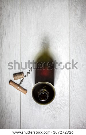 Bottle of red wine with cork on white wooden table. Top view - stock photo