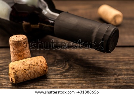 Bottle of red wine with corks lying on an old wooden table. Close up view, focus on the bottle of red wine - stock photo