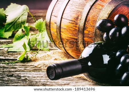 Bottle of red wine with fresh grape and wooden barrel - stock photo