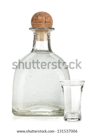 Bottle of silver tequila and shot with lime slice. Isolated on white background