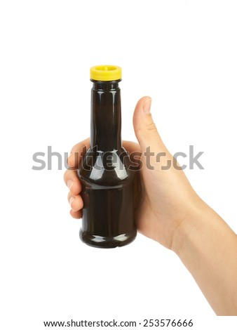 Bottle of soy sauce in the hands isolated on white background - stock photo