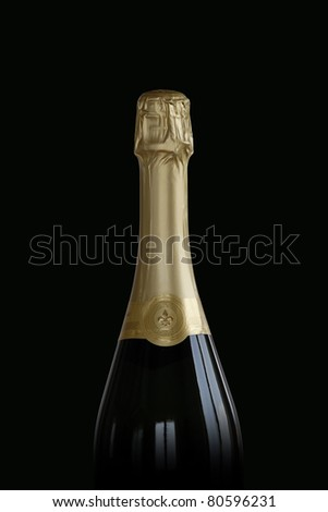 Bottle of sparkling wine against black background - stock photo