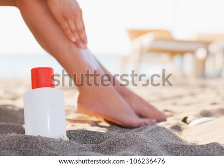 Bottle of sun block and female applying creme on leg on beach - stock photo