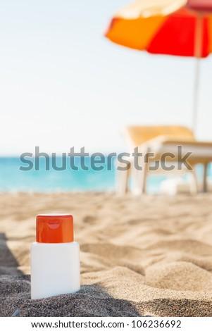 Bottle of sun block creme in shadow on beach - stock photo