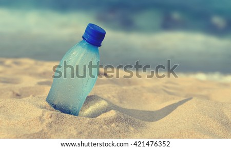 Bottle of the fresh water on the beach - stock photo