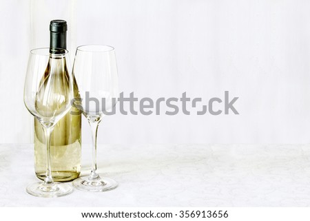 Bottle of vine and two empty glass is stand on the white tablecloth