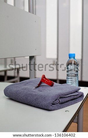Bottle of water and towel in locker room - stock photo