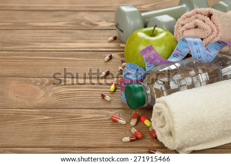 Bottle of water, apple and measuring tape on a brown background - stock photo