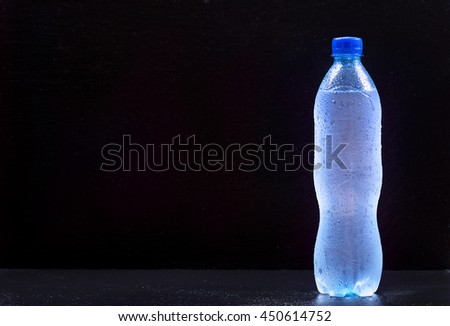 bottle of water on dark background - stock photo