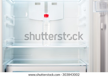 Bottle of water on shelf of open empty refrigerator. Weight loss diet concept. - stock photo