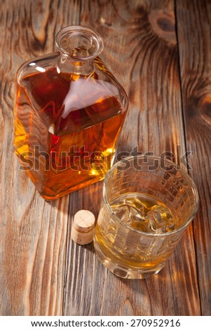 Bottle of whiskey and a glass on a wooden table - stock photo