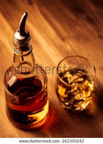 Bottle of whiskey with a metal pourer and a filled glass - stock photo