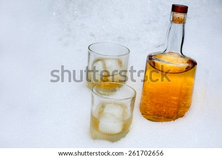 Bottle of whiskey with two glasses in the snow - stock photo