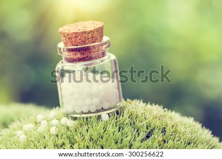 Bottle of white homeopathy globules on green moss. Retro styled. - stock photo