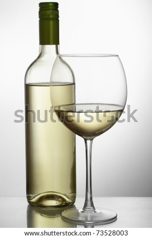 Bottle of white wine and glass over light grey background