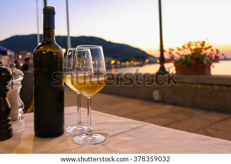 Bottle of white wine and two glasses on the restaurant table on sunset - stock photo