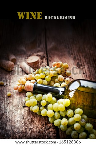 Bottle of white wine, grape and corks on wooden table - stock photo