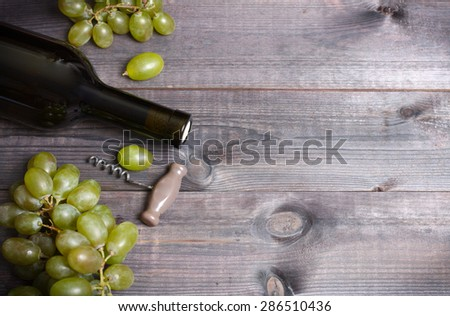 Bottle of white wine, grape and corkscrew on wooden table - stock photo