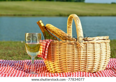 Bottle of white wine in picnic basket with glass of wine beside it.  Red gingham blanket and napkin with lake in background. - stock photo