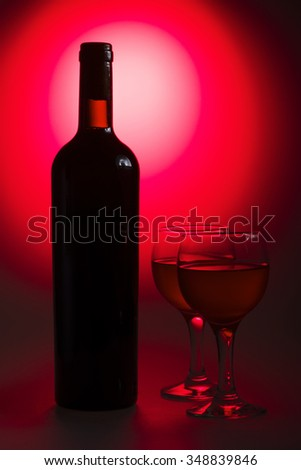 Bottle of white wine with glass on red background - stock photo
