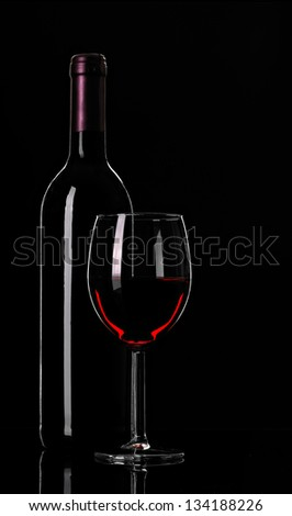 bottle of wine and a glass wine on black background - stock photo