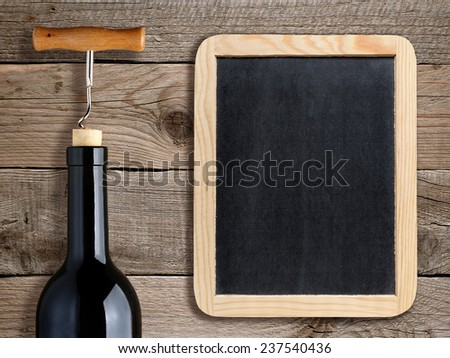 Bottle of wine and blank blackboard on wooden background - stock photo