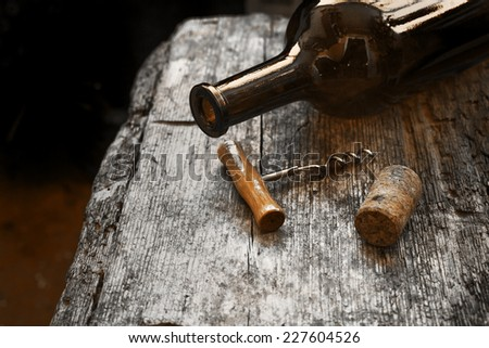 Bottle of wine and cork and corkscrew on wooden table - stock photo