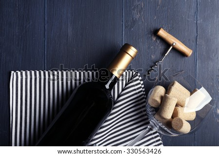 Bottle of wine and corks on wooden table - stock photo