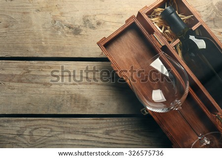 Bottle of wine and empty glass in case on wooden table - stock photo