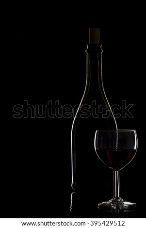 Bottle of wine and glass with red wine on a black background, silhouette, studio lighting, minimalism
