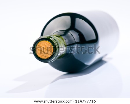 bottle of wine and its shadow. lying on white base - stock photo