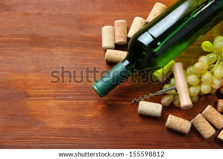 Bottle of wine, grapes and corks on wooden background - stock photo
