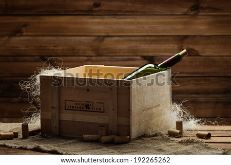 Bottle of wine in box in wooden interior  - stock photo