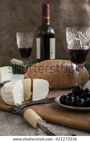 Bottle of wine, olives, cheese and white bread are on sacking