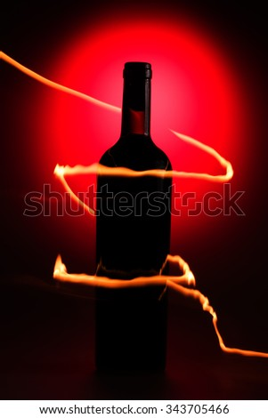 Bottle of wine on the red background with flames - stock photo
