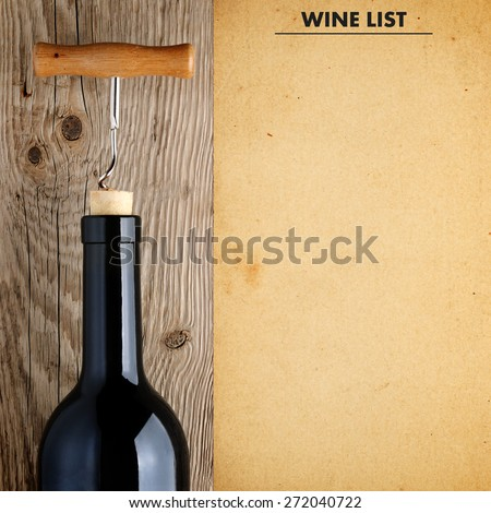 Bottle of wine with corkscrew and wine list - stock photo