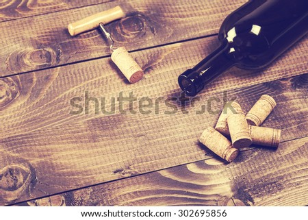Bottle of wine with corkscrew on wooden background - stock photo