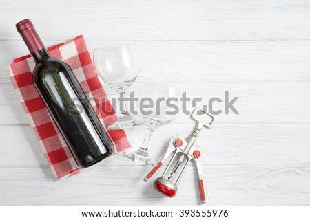 bottle of wine with wine glass on white wooden background. - stock photo