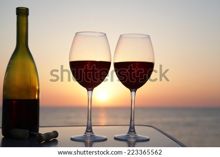 Bottle of wine with wine glasses at sunset on the sea background - stock photo