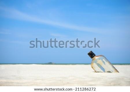 Bottle on a sand beach - stock photo