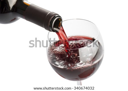 bottle pouring red wine into glass on white background