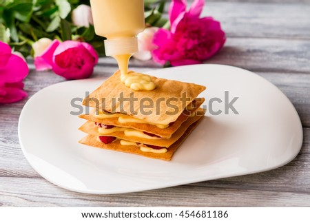 Bottle putting custard on shortcake. Pink flowers in the background. Ingredients for pastry. Dessert with sweet filling. - stock photo