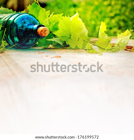 Bottle, vine and corks on wooden table/ Summer wine background - stock photo