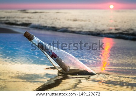 Bottle with a message thrown by the sea - stock photo