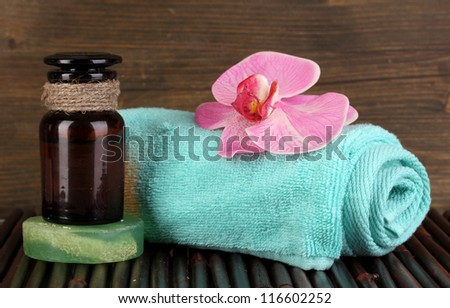 Bottle with aromatic oils with accessories for relaxation on wooden table on wooden background - stock photo