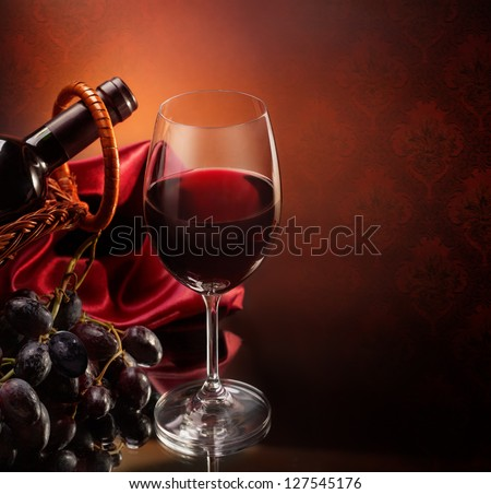 Bottle with bunch of grapes and wineglass of red wine