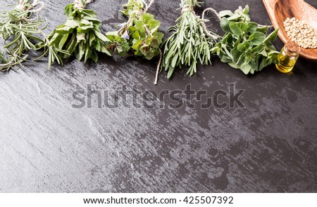 Bottle with herbs on black stone background. Mint, thyme, balm and other medicinal herbs