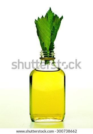 bottle with homeopathy balm and leaf - stock photo