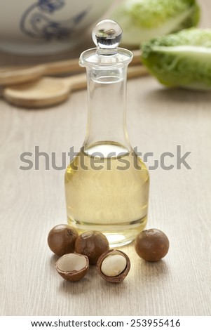Bottle with macadamia oil and nuts - stock photo