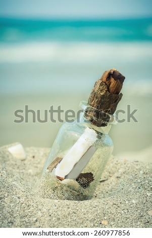 bottle with message on sand beach over blue sea background. - stock photo